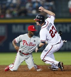 Atlanta Braves' Chris Johnson (23) steals second base as Philadelphia Phillies shortstop Jimmy Rollins (11) applies the late tag in the third inning of a baseball game.