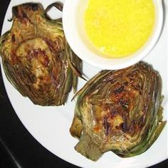 Grilled Garlic Artichokes | No more dipping artichokes in mayo! These artichokes are grilled with a lemon garlic basting sauce. This is the best way to eat artichokes.