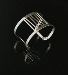 Grass Cuff Bracelet in Chrome by Melissa Stiles. Lightweight and flexible cuff bracelet is made from stainless steel and is coated in a shiny chrome finish. This gives it the look of polished silver, but it will never tarnish or need to be polished.
