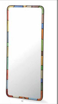 """162 — FONTANA ARTE Grand miroir rectangulaire bordé d'une doucine translucide laissant apparaître une composition de baguettes de miroirs colorés verts, bleus, roses et jaunes, incrustées dans le châssis en bois teinté noir. Pattes de fixation en laiton. Étiquette """"Galvanit Fontana - Luigi Fontana"""". A mirror with coloured mirrored glass frame. HAUT. 147 CM - LARG. 59 CM - PROF. 19 CM / HEIGHT. 57 7/8 IN. - WIDTH. 23 1/4 IN. - DEPTH. 7 1/2 IN. 3 000/4 000 € Bibliographie : Franco…"""