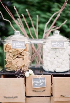 Perfect for an outdoor wedding that can host a fire pit, this s'mores treat display keeps in tune with the neural theme by showcasing fluffy white marshmallows and honey graham crackers in clear jars.