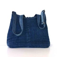 This cross body bag is made out of a jean pant.  It has a V-shape opening, and wider base with pleating. This bag is fully lined with a pale yellow and green cotton print. It features 2 exterior pockets on the front side ,and 2 interior pockets. Metal button and fabric loop keep the opening closed. Metal slider provides different options for strap length.  Measurements: top width:12.5(32cm) base width:15(38cm) height:12(30cm) depth: 2 (5cm) strap: up to 49 (124) Machine washable and dryable