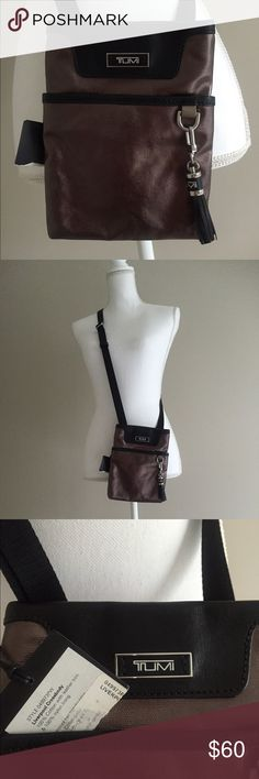 """NWT Tumi Liverpool Cross Body bag with tassel New with tags. Pewter (dark silver with gold undertones) cross body with leather tassel. Tassel is detachable. Bag dimensions are 8.5"""" by 6.5"""". Magnetic closure on main compartment and front pocket. Back pocket is open (no closure). Interior of bag is one open section. No interior pockets. Really high quality piece, perfect for traveling. Tumi Bags Crossbody Bags"""