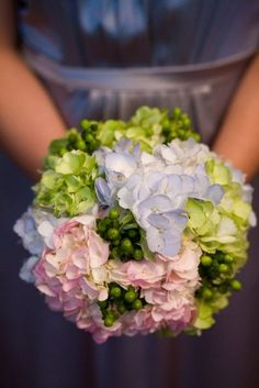 bridal bouquet of pink, blue and green hydrangeas and green coffee berry