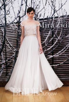 "Brides: Mira Zwillinger - 2014-2015 Collection. ""Daria"" two-piece silk and lace A-line wedding dress with an illusion high neckline, cap sleeves, and bare midriff, Mira Zwillinger"