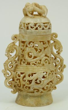 """Archaic style Chinese carved jade vase having reticulated body and cover depicting mythical beasts. Has reticulated beast handles to sides. Measures 5"""" height x 3 1/2"""" width (12.7cm x 8.9cm)."""