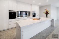 White gloss cabinets, marble island bench, smoked mirror splashback and polished concrete flooring - all add up to a big wow factor!