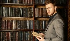 Well dressed man reading book in front of book shelf