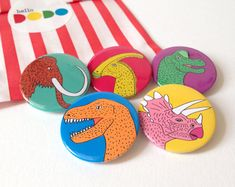 This is a pack of 4 bright and fun Dinosaur button badges and 1 Wooly Mammoth! Perfect for Dinosaur lovers of all ages, these badges are guaranteed to make your outfit more ROARsome! A great idea for Birthday pressies or kids party bag fillers. Custom Button Pins, Custom Buttons, Badges, 23 November, Badge Design, Button Badge, Party Bag Fillers, Dinosaur Party, Pin And Patches