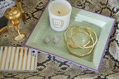 Gold bamboo bangles, dainty earrings and Jasmin candle look neat and tidy on a small tray. The Zhush