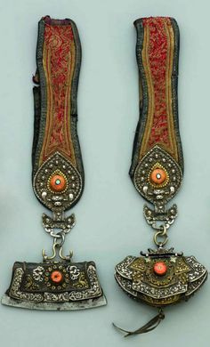North Eastern Tibet | Two leather, silver and brass belt hangings from Amdo (North EasternTibet). The flint and tinder pouch and the coin purse belonging to the same belt. The loops of silk brocade with silver mounts, cast in relief, each chased with a 'kirtimukha' and two hands, the centre with turquoise and coral in a gilt metal setting. Both embossed and engraved silver and brass with coral. The flint and tinder pouch with iron strike and partial gilt work | 1930s. | Est 900€ ~ (June '13)