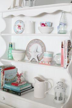 beach cottage dresser full of china, starfish, bottles, books and flowers...