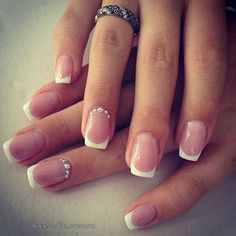 Beautiful silver bead studded French tip nails. The nails start off with the natural clear polish base and finished with a thin white polish tip shaping the square nails. Additional silver beads are also added on the inner edge of the nails.