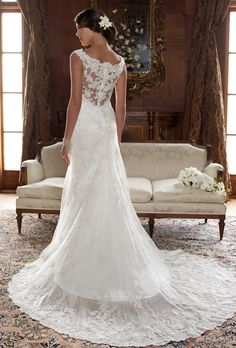 Casablanca Bridal 2004 Beaded lace appliques sewn on netting over crystal satin lining. Off-the-shoulder neckline with scalloped trim accent. Fit-and-flare A-line silhouette.