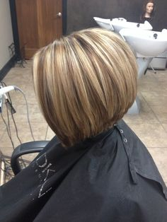 Honey blonde with a warm neutral lowlight. Haircut is a slightly inverted bob.