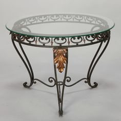 Italian Glass Top Table With Green Iron Frame and Gilt Metal Leaves  --  Circa 1930s Italian round glass top table has a curvy iron frame with green finish, decorative scroll work accented with gilded arrow points, three legs topped with gilt metal leaves.   --   Item:  6774  --  Retail Price:   $795