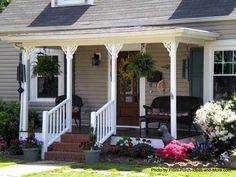Small front porch with wind chimes and wicker furniture epitomize cottage living. front-porch-ideas-and-more.com #frontporch
