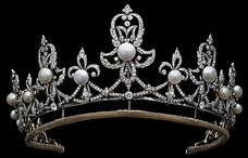 British: The Raine Spencer Tiara. The tiara is made of diamonds set in fleur-de-lys motifs, the center of which are studded with large pearls. Raine has been photographed wearing the piece both as a tiara and a necklace. It's not clear when it was made, but the design does suggest a twentieth-century creation date. Raine did have access to both of the Spencer family's other tiaras during her second marriage, so perhaps this tiara is one that she purchased on her own after she was widowed?