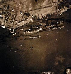 "80-G-387566: Pearl Harbor Attack, 7 December 1941. Aerial view of ""Battleship Row"" moorings on the southern side of Ford Island, 10 December 1941, showing damage from the Japanese raid three days earlier. Shown are: USS Oklahoma (BB-37), capsized; USS Tennessee (BB-43), lightly damaged, with the sunken USS West Virginia (BB-48). Note dark oil streaks on the harbor surface, originating from the sunken battleships. Photographed by VJ-1 at an altitude of 3,000 feet and released November 9…"
