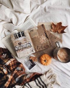 fall and autumn aesthetic | white sheets and bedding, cozy plaid blanket, pumpkin, leaves, mug with hot chocolate, notebook of illustrations and drawings