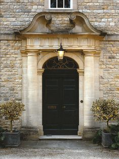 Beautiful old stone, potted trees, and a double front door