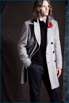 Ryan Keating wears a herringbone topcoat, wool bomber jacket, foulard shirt, tie, and striped trousers from Club Monaco.
