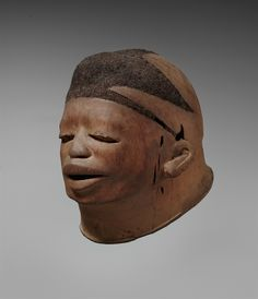 A MAKONDE HELMET MASK  Tanzania/Mozambique  With asymmetrical shaved head inset with human hair, hooded eyes and pierced mouth, dark patina.  24 cm. high