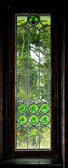 A beautiful stained and leaded window in the English Arts & Crafts style, using clear glass and green 'bottle' glass rondels. This window is in a house designed by the prominent British Columbia architect Samuel Maclure. The design is directed by the shape of the available coloured glass.