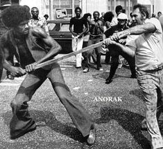 A member of the Ku Klux Klan and black man struggle over possession of a stick during an encounter in downtown Mobile, Alabama, Saturday, Sept. 24, 1977. A large group of blacks disrupted the Klan's march, resulting in at least two encounters between the two groups