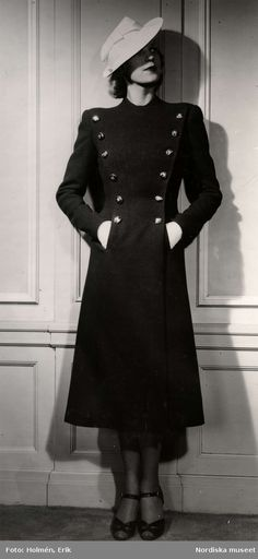 Dammode 1938. En kvinnlig modell poserar med en mörk dubbelknäppt kappa och hatt. Foto: Erik Holmén för Nordiska Kompaniet.