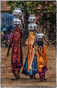 Meninas indianas de vila no estado de Gujarate, Índia, vestidas em roupas típicas, carregam jarros de água.  Fotografia: Rosemary Sheel.