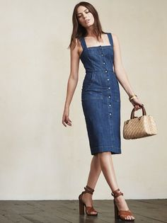 This is part of the Reformation x Jeanne Damas collection. Oh la la, the Winfield Dress. This is like finding the perfect pair of jeans that fit like a glove, except for your whole body. This is a knee-length denim dress with a snap button up front and front pockets. The straps cross in the back and there's also a small slit in the back. Hugs the body, so you can show what you've got. But, you know, in the most casual way. Made from surplus denim.