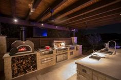 The outdoor entertaining area of this family home features a large inground pool with a nearby dining area. In addition, the space has a fully loaded gourmet kitchen with smoker, sink, refrigerator, and pizza oven. Ceiling fans help keep guests cool as they watch the outdoor TV.
