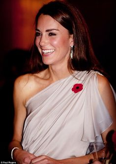 The Duchess looks glamorous in her Grecian style dress, coupled with the all important poppy. She also added some sparkle with some bold earrings