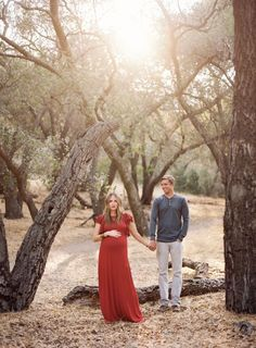 Forest Maternity Session, couple, hand holding, sunlight, forest, red dress, gray shirt, baby bump