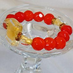This #vintage art glass gold and carnelian red bracelet is fabulous!  It features a large square clear art glass bead filled with gold foil, surrounded by carnelian orange r... #ecochic #etsy #jewelry #jewellery