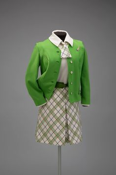 Created for TWA by knitwear maker Dalton Apparel, this uniform was introduced in the summer of 1968 and worn until 1971. Made of Trevira polyester, the green collarless jacket has dropped cuffs. The short-sleeve dress, worn with a green tapered belt, has a plaid skirt with a front kick pleat and a solid top with collar. An attached neckerchief with a ring matches the skirt. SFO Museum Collection Gift of TWA Clipped Wings International, Inc. Jacket insignia: Anonymous lender