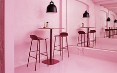 Form barstools and table surrounded by chic pink