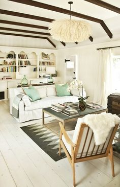 nice livingroom in white and other light colors, low ceiling but well used