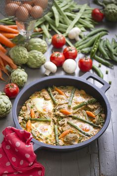 Cazuela de verduras. Ingredientes (para 4): 300 gr. de guisantes tiernos 6 alcachofas 200 gr. de judías verdes 2 zanahorias 1 manojo de espárragos verdes 4 cucharadas soperas de tomate frito 100 gr. de Vivesoy 8 nueces 1 diente de ajo 1/2 cebolla Sal 3 cucharadas de aceite de oliva virgen extra 1/2 cucharada de harina 4 huevos