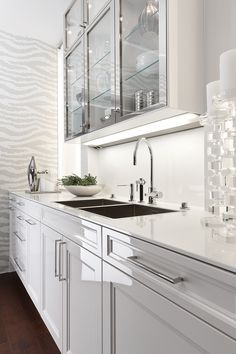 Sleek, glossy kitchen cabinets in lotus white from the SieMatic Beaux Arts Collection.
