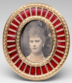 This Fabergé frame contains a photograph taken in 1897 when Queen Mary was Duchess of York. The frame is of yellow and red gold with laurel leaves around the bezel and the edge of the frame, containing a panel of red guilloché enamel. It is backed with ivory and fitted with a gold strut. Mark of Michael Perchin.
