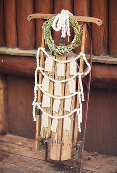 An escort card display made out of an antique sleigh is decorated with a dainty wreath and hanging cards | Brides.com