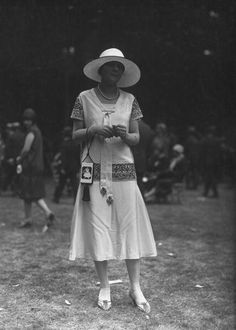 A woman wearing a silk dress and matching picture hat at the races. #vintage #fashion #1920s