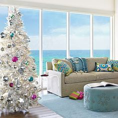 Tropical White Christmas Tree  - Even if you don't live in a snowy locale, you can imitate a white Christmas with a pretty white tree. Silver trinkets add sparkle to a stark base, while tropical ornaments lend fun pops of color.  20 Charming Coastal Christmas Trees | White Christmas | CoastalLiving.com