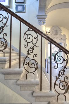 Delicately beautiful stair rail sitting, probably, on marble stairs. Look beyond to the awesom carved doorway. Got to be a very rich house.