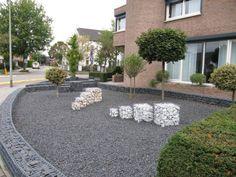 Vorgarten Idee mit Splitt in grauer Farbe und Gabionen-Dekos