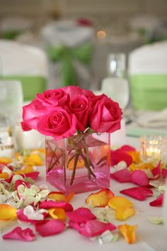 bright pink roses in pink glass cube with assorted color petals scattered on table top