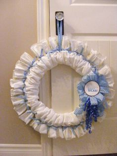 Diaper wreath for baby shower.  This would be cute with prefolds dyed in various colors, or cloth wipes.  Cute!  :)
