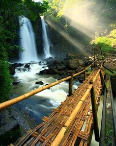Beauiful photograph - sunbeams, waterfall and handmade bridge across the river! Amazing.